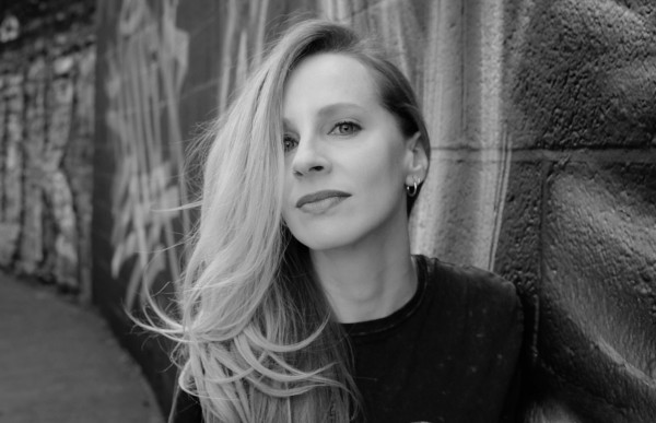 Greyscale. Natasa Paulberg, a white woman, standing side on against a wall, looking at the camera. Her long blonde hair is swept over one side of her face over her eye.
