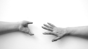 Greyscale. Two arms reaching for each other. The hand on the left has two fingers on opposite ends of the hand.