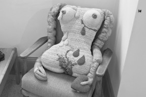 Greyscale. A large knitted replica of a woman's torso and arms. One arm is clutching a knitted heart, and one nipple is leaking milk. There is also blood and scars on her body.
