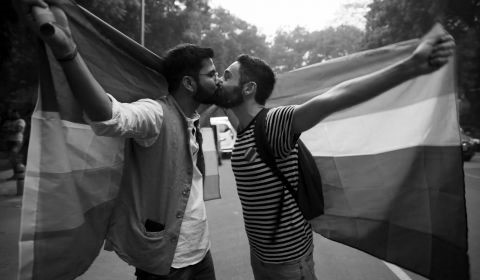 Greyscale. Two men kissing, holding a large pride flag up behind them.