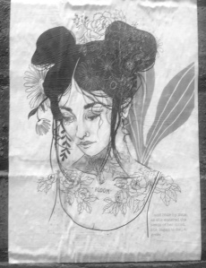 Greyscale. A woman looking down as wisps of hair fall in her face. She is tattooed with flower patterns and has dark hair up in two buns. She has flowers in her hair and there is a plant behind her.
