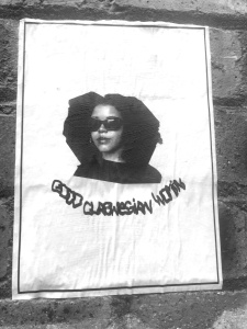 "Greyscale. A picture of a Black woman head and shoulders down. She has an afro and is wearing sunglasses. Under this are the words ""good glaswegian woman"" in stylised caps. The image is attached to a brick wall."