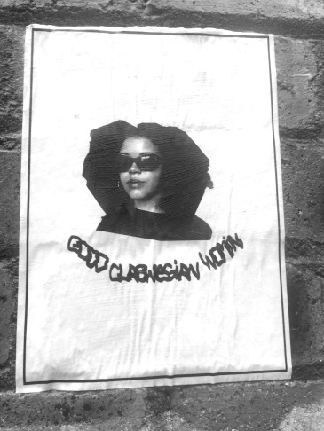 """Greyscale. A picture of a Black woman head and shoulders down. She has an afro and is wearing sunglasses. Under this are the words """"good glaswegian woman"""" in stylised caps. The image is attached to a brick wall."""