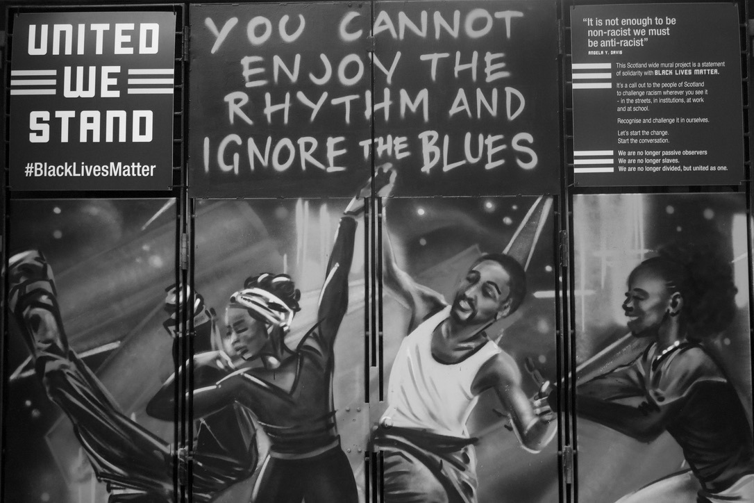 """Greyscale. A mural-painting of black people dancing at a disco. Above this is the phrase """"United we stand #BlackLivesMatter,"""" """"You cannot enjoy the rhythm and ignore the blues"""" and the Angela Davis quotation """"In a racist society it is not enough to be non-racist, we must be anti-racist."""""""