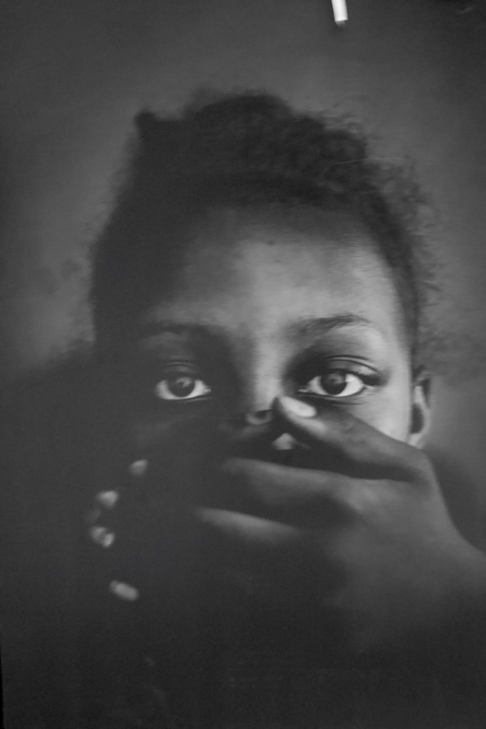 Greyscale. A closeup of Lola, a black girl, with her hand clamped over her mouth.