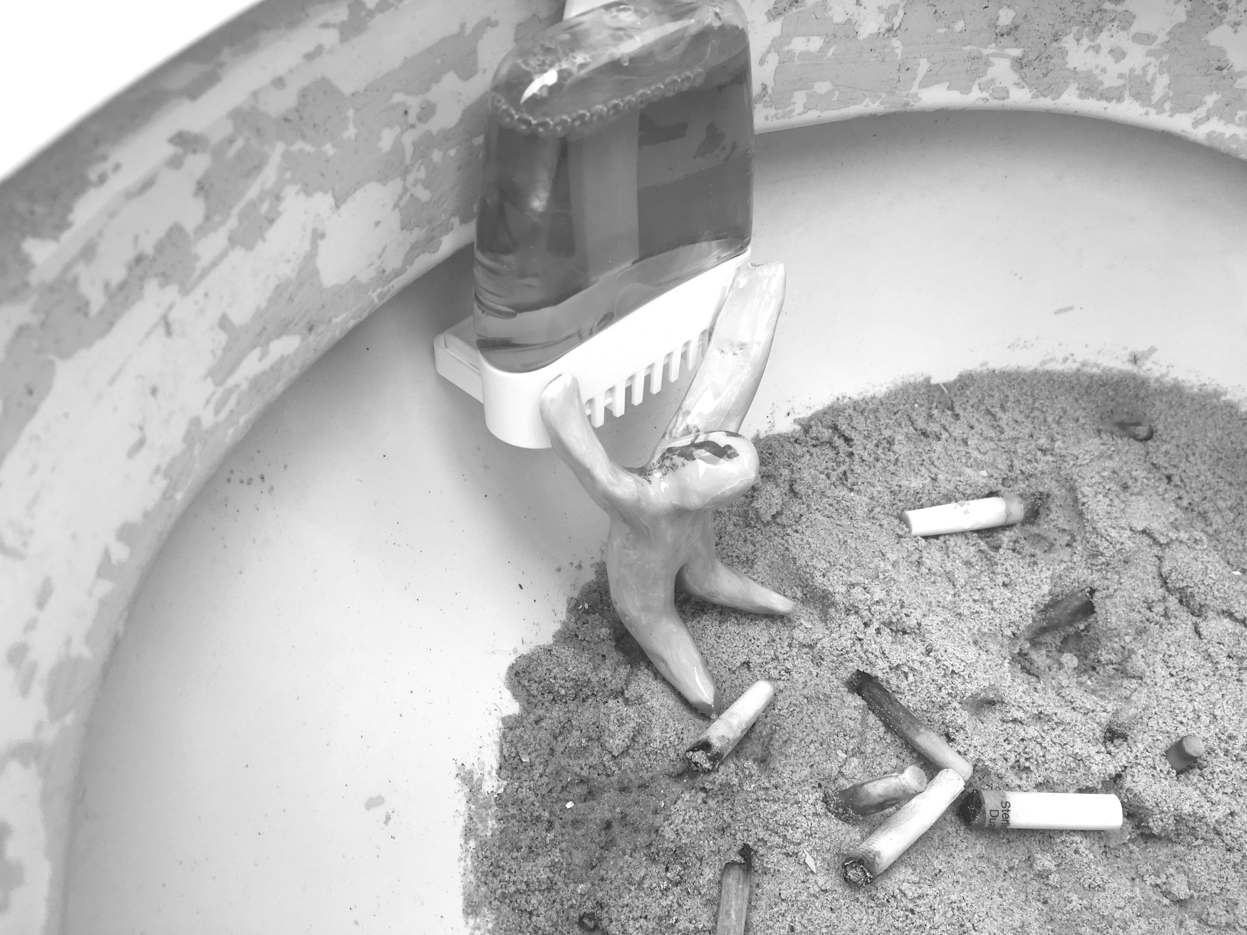 A clay figure in an ashtray full of cigarettes and ashes, on its knees with its hands up.