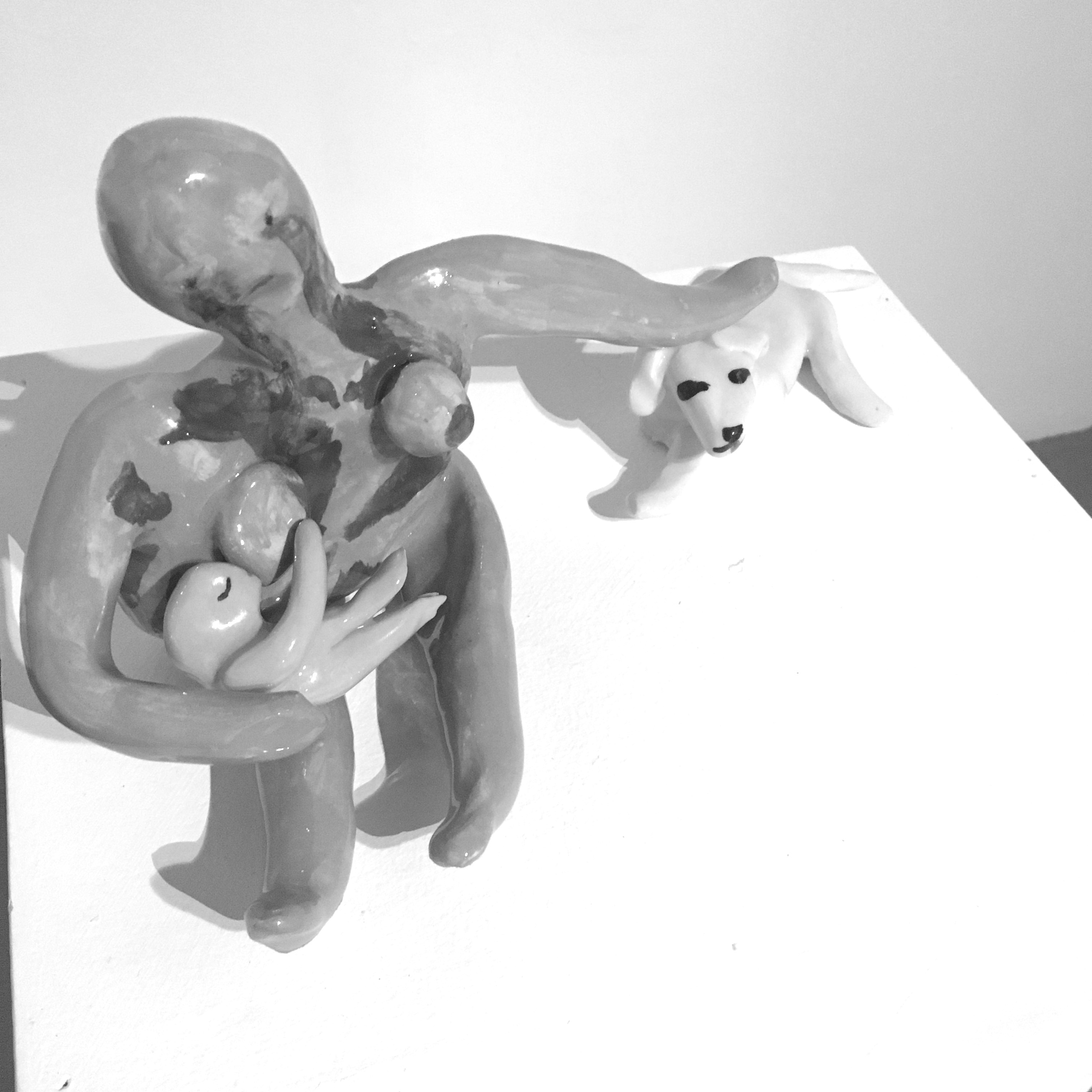 A clay figure of a woman holding a baby as she breastfeeds and pets a clay dog.