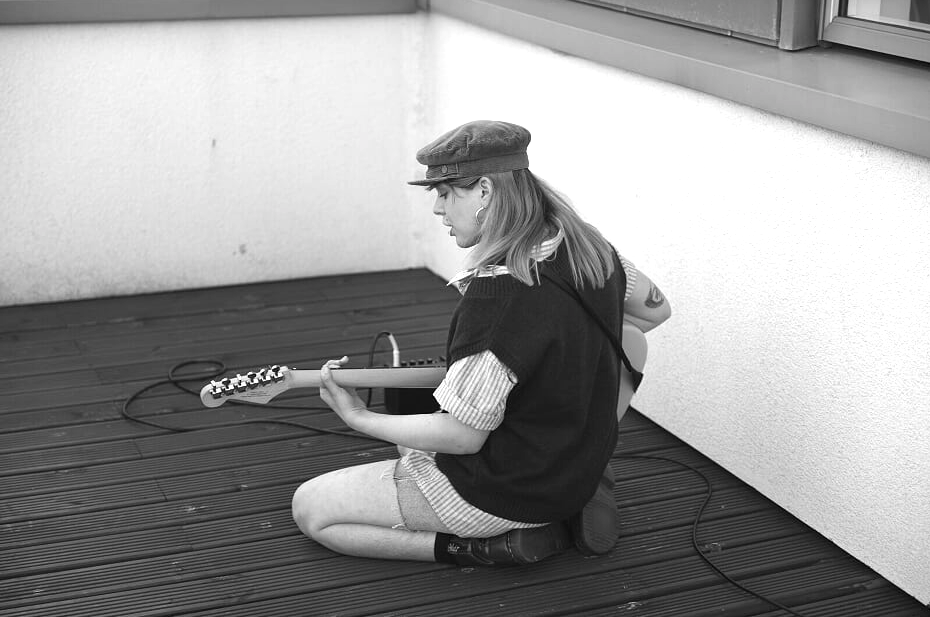 Greyscale. Chloe Segall kneeling on a wooden deck playing an electric guitar.