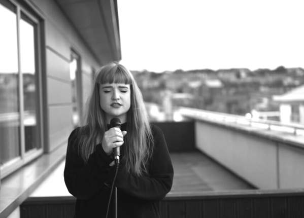 Greyscale. Katherine Allan, a white woman with long red hair, singing into a microphone on a rooftop.