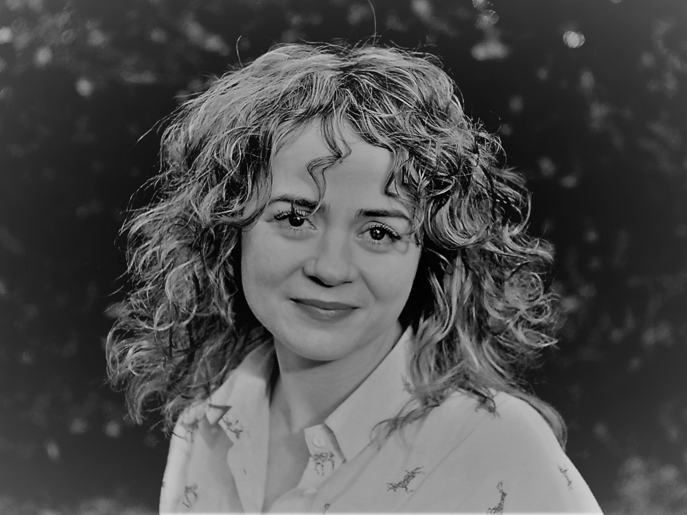 Greyscale. Maureen O'Connell, a white woman with shoulder-length wavy hair, smiling slightly at the camera.
