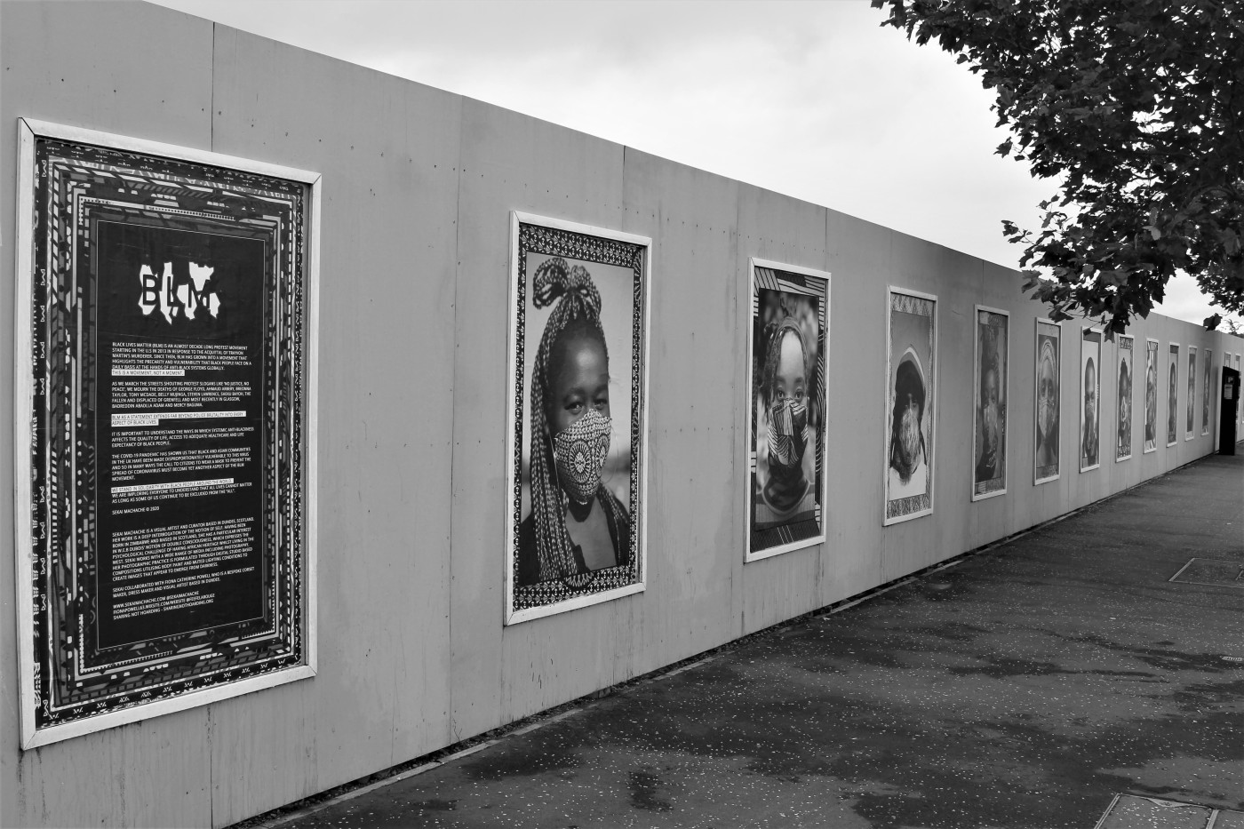 Greyscale. A mural in Dundee where large pictures of Black people wearing facemasks, framed in various patterns.