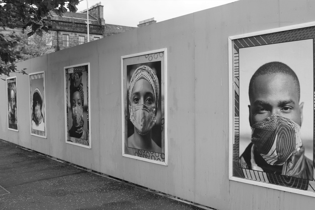 Greyscale. A mural of multiple photos of Black people wearing facemasks. The patterns on their facemasks matches the borders of the pictures.