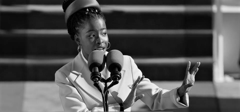 Greyscale. Amanda Gorman, a black woman, speaking in front of a large microphone, looking and gesturing to the side.