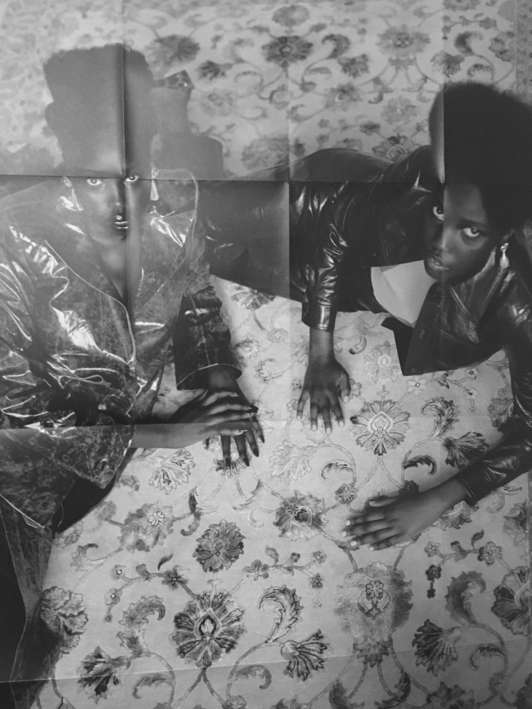 Two Black women lying on a couch.