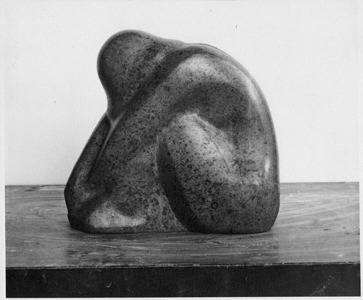 Greyscale. this sculpture shows a figure hunched over their own knees, head bowed. The piece feels cramped and full of sorrow.