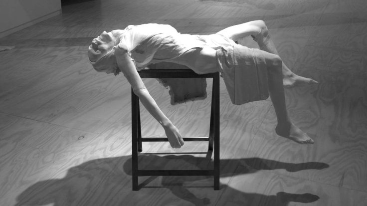 Greyscale. both images show the same sculpture of a half-flayed woman collapsing in pain.