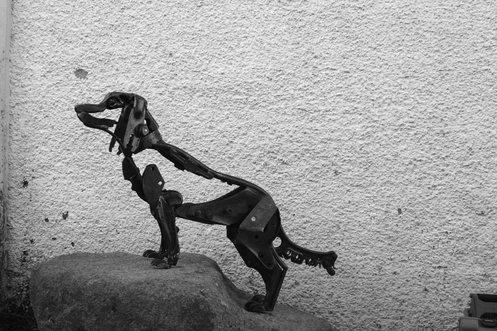 Greyscale. This scrap metal sculpture of Jasper the Dachshund shows him climbing on rocks as if travelling to his late master. While the dog's legs are fairly solid, his body and face are more of an outline. This gives the effect of an ink pen sketch rather than a 3D sculpture.