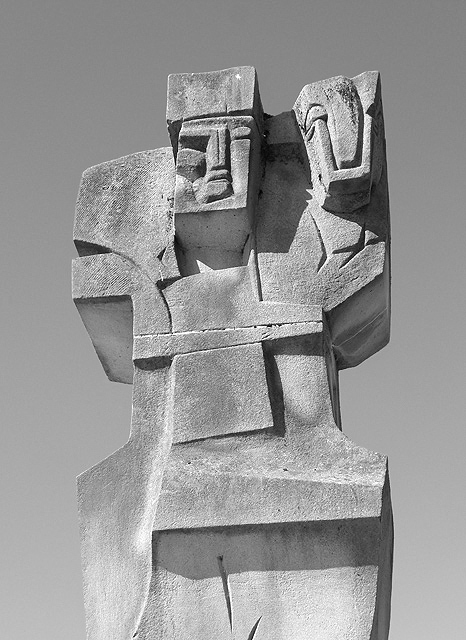 Greyscale. this carved stone sculpture shows a man with a sheep across his shoulders. His face is contorted with the effort, eyes squinting in the sun. The piece is abstracted in a cubist style.