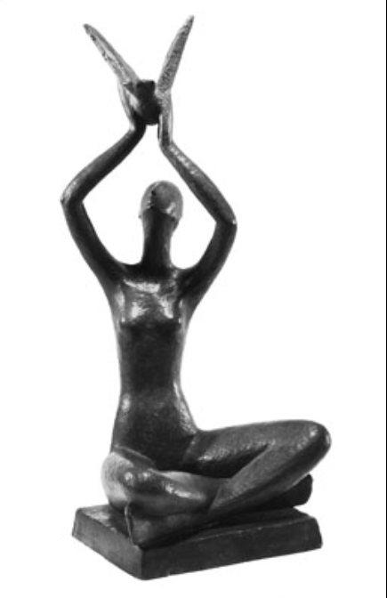 Greyscale. A small bronze sculpture of a woman holding a bird above her head. She sits cross-legged, gazing towards the bird whose wings are opening in flight. The sculpture is simplified, the woman is bald and her figure is elongated. The piece is peaceful and hopeful.