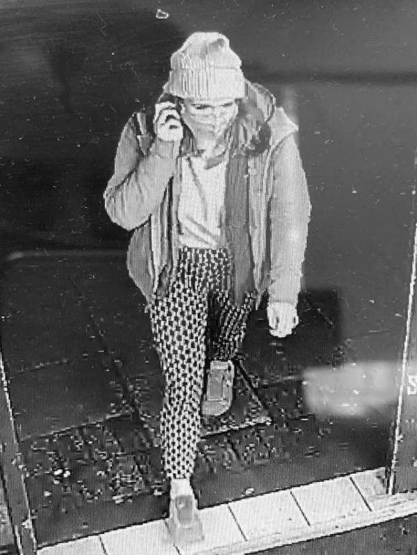 CCTV image of Sarah Everard. She is shown walking, on the phone, wearing a coat, scarf and hat and sensible shoes.