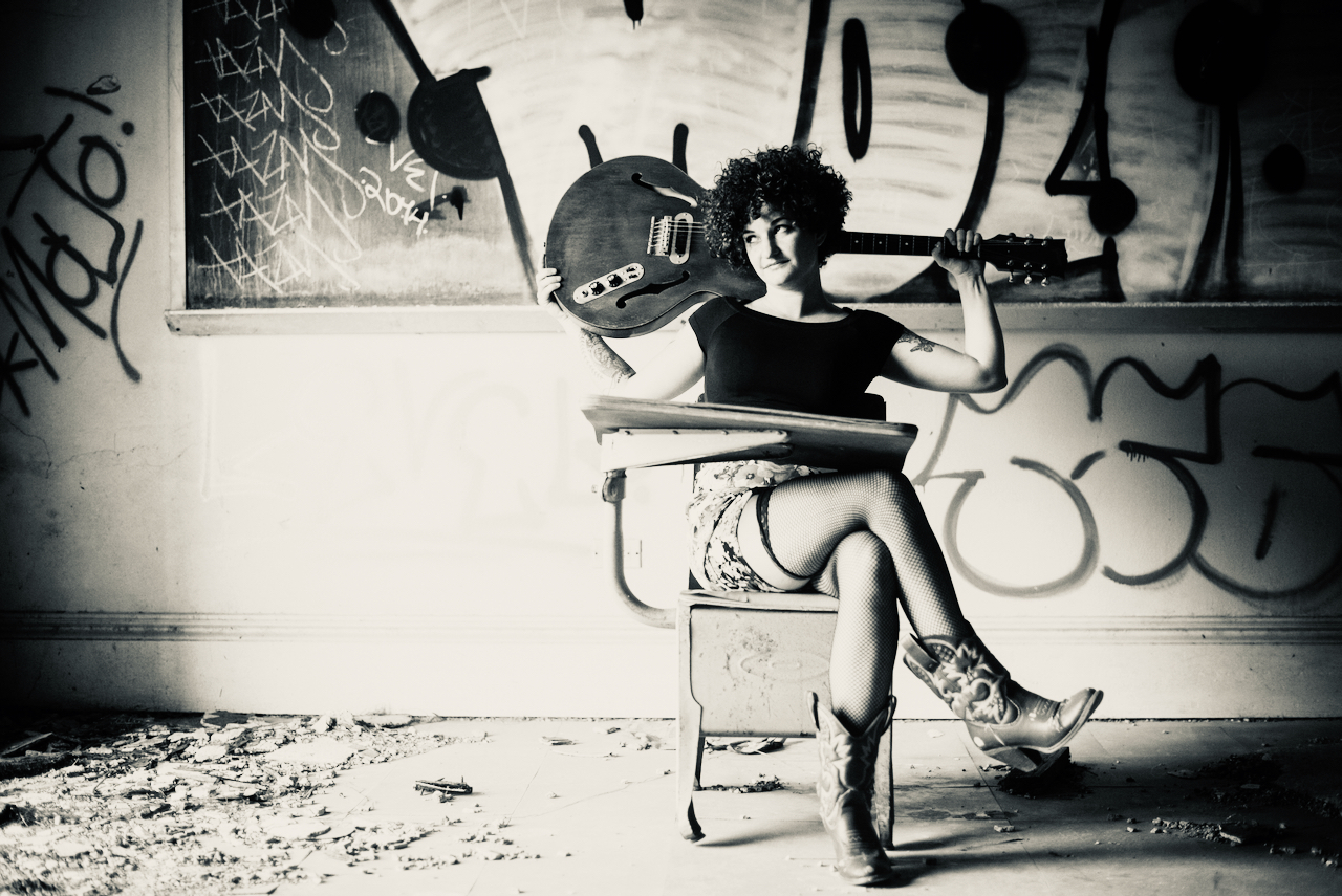 Greyscale. Carsie Blanton, a woman with short curly hair, sitting in a chair with her legs crossed, holding a bass behind her head. She's sitting in front of a wall of graffiti.