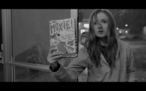 "Greyscale. The film's protagonist, 16-year-old Vivian, holds up a copy of the Moxie zine. A white girl, with long blonde hair, she looks earnest and naive - though the graphic design on the front cover is bold. The free zine shows a white girl with boxing gloves on with the headline, ""The Girls Of Moxie Are Over It!"""