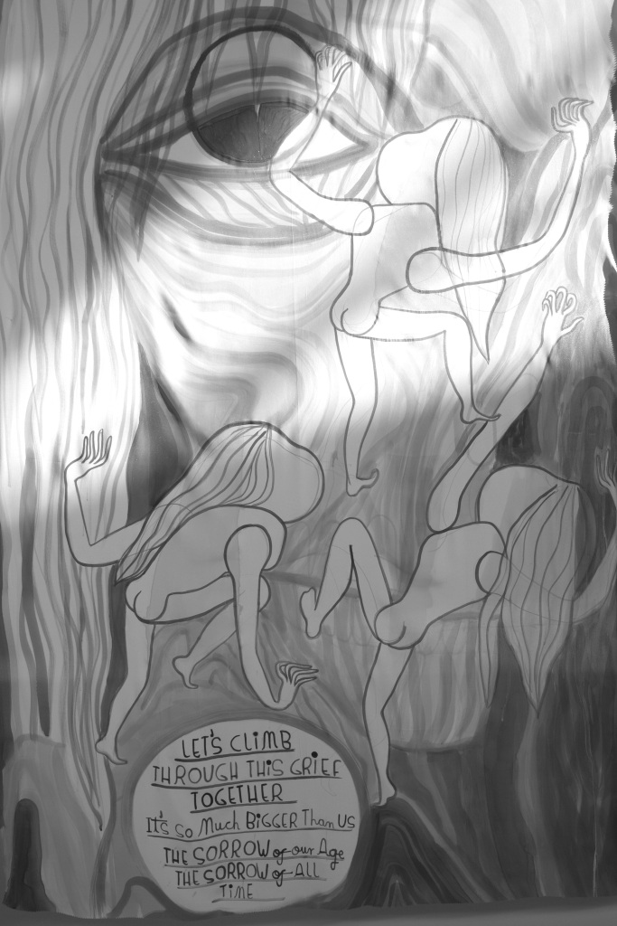 """Greyscale. Three naked female figures climb up the lined face of an older woman, one eye visible and open. A text bubble reads: """"Let's climb through this grief together. It's so much bigger than us. The sorrow of our age, the sorrow of all time."""" A shaft of light cuts through the image, as daylight shines from the overhead windows."""