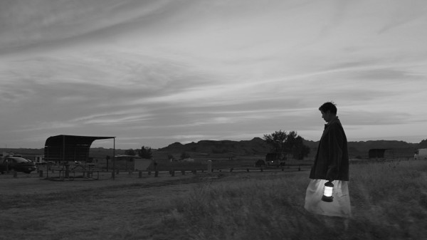 Greyscale. A woman carrying a lantern, walking across a field to a fence.