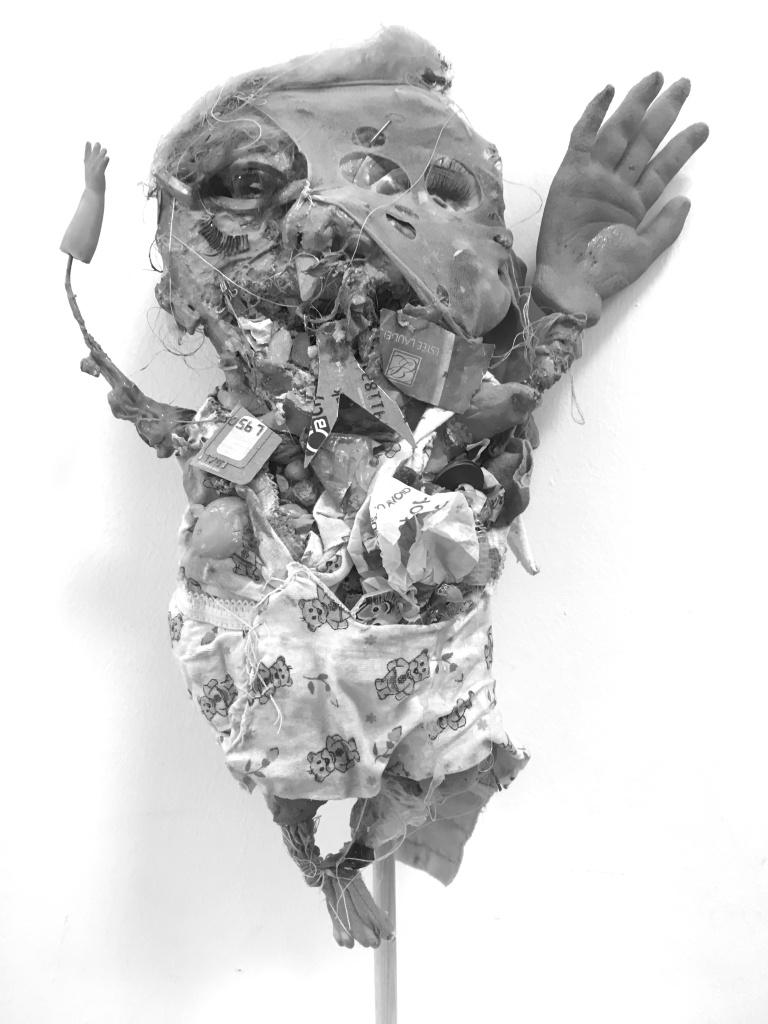 A disturbing plastic clay mixed-media piece.