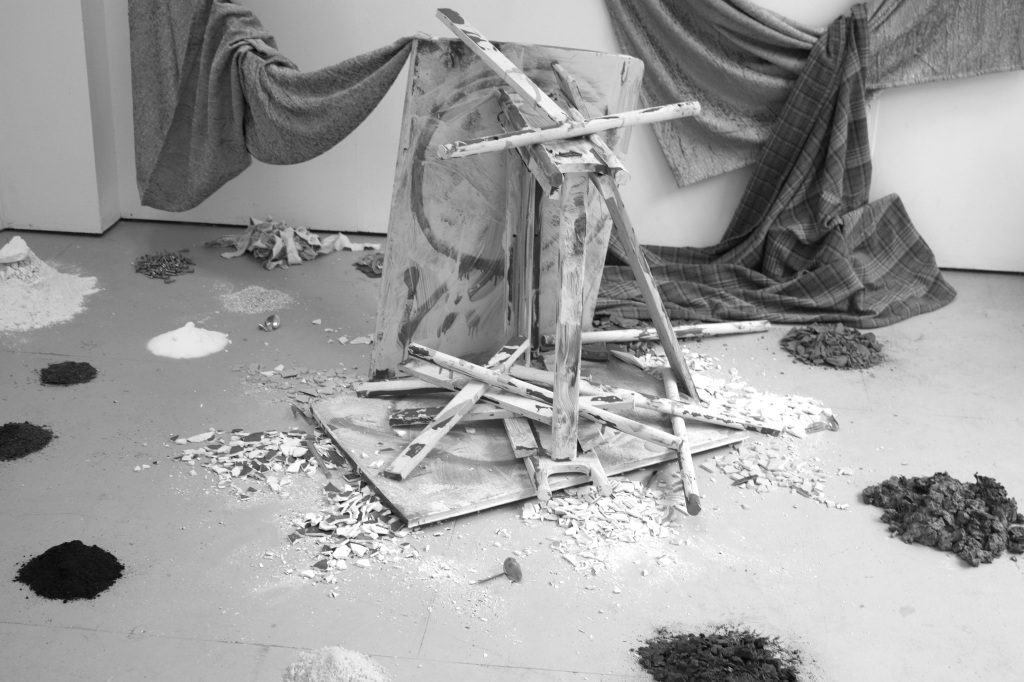 Greyscale. Pieces of wood are piled in the centre of a gallery floor, surrounded by small mounds of earth and salt. In the background hang fabric haphazardly
