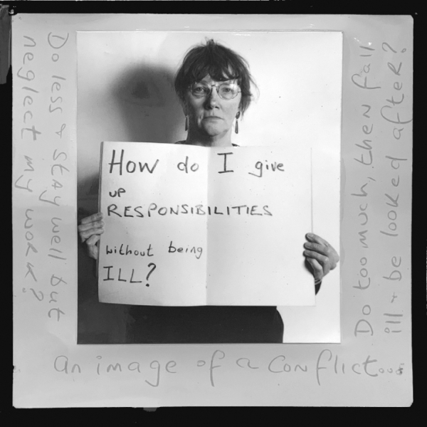 """Alt Text: The artist, Jo Spence, stands against a plain white background holding a sign that says, """"How do I give up responsibilities without being ill?"""" She is white and middle-aged, with brown hair, glasses, long earrings and a solemn expression. The photograph has been placed on salmon pink paper, on which Spence has scribbled various thoughts and questions. From the left they read: """"Do less & stay well, but neglect my work? An image of conflict. Do too much, then fall ill & be looked after?"""""""