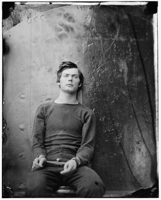 Alt text: A black and white photograph of Lewis Payne, a young American Confederate soldier who was involved in the assignation of President Lincoln. Here he is waiting to be hung, staring past the photographer, Alexander Gardner, with a look that could be interpreted as resignation or despair.  He wears a thin jumper and trousers, with his hands manacled in front of him, leaning his back on the metal wall of the prison warship.