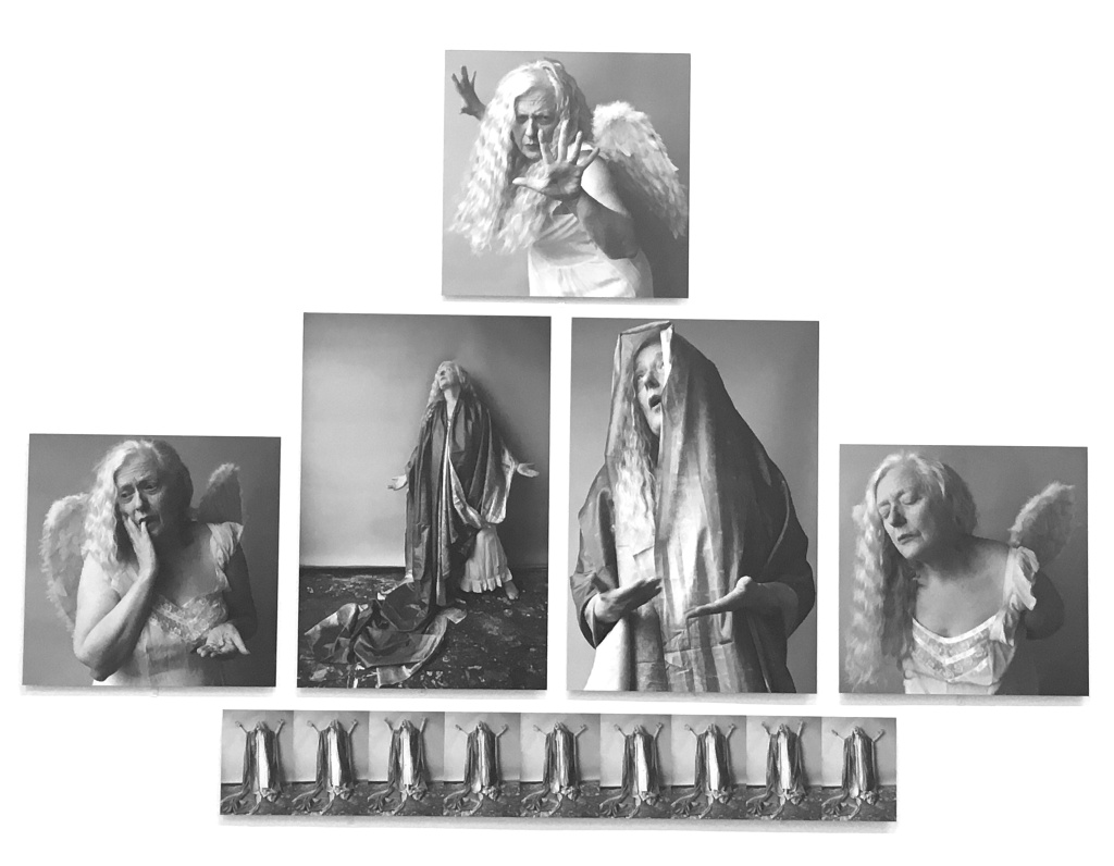 Alt Text: The artist, Rosy Martin, strikes various theatrical poses dressed, alternatively, like the Virgin Mary and as an angel. Her expressions are exaggerated. Martin is an older white lady with long grey hair. The backgrounds are grey and the photographs are arranged in a pyramid shape.