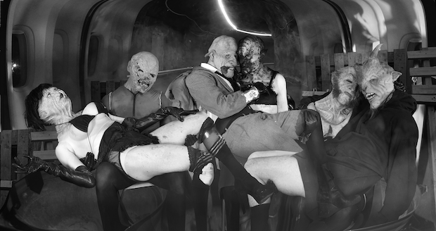 Six grotesque humanoid creatures, in various stages of undress, cuddle into each other. Paired off, the figure in the centre holds a rose between his teeth. They are in some sort of abandoned aircraft carrier and their animalistic faces are twisted, through their bodies are unblemished. The atmosphere is of a particularly raucous nightclub.