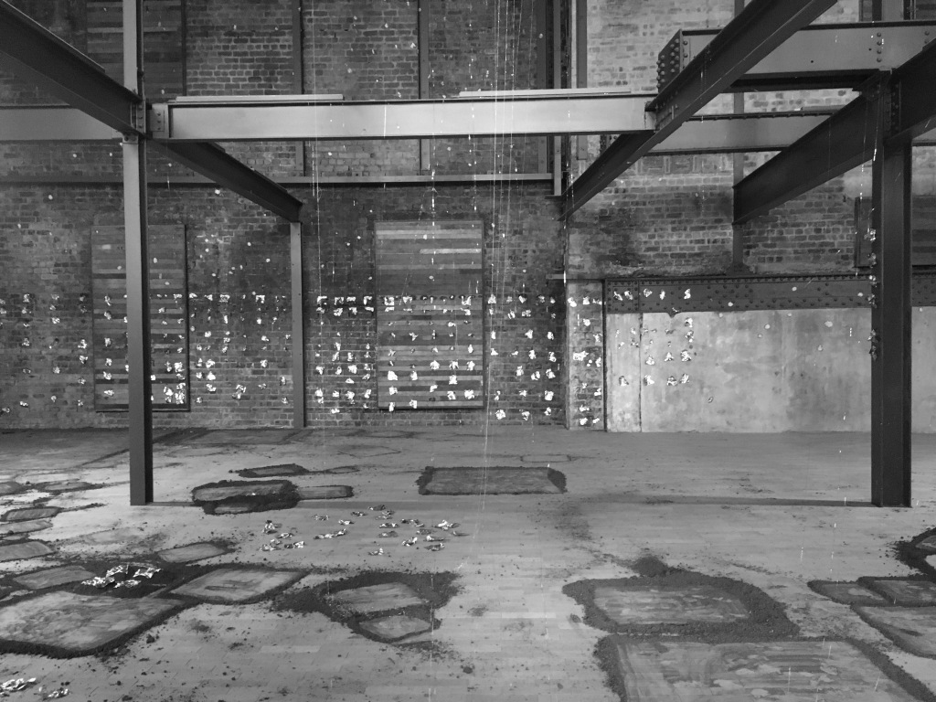 within the warehouse space, with its exposed brick, industrial beams, and dark wood, Black has hung pieces of gold and copper leaf in the air, left squares of earth on the floor, and smeared vasaline on the walls.
