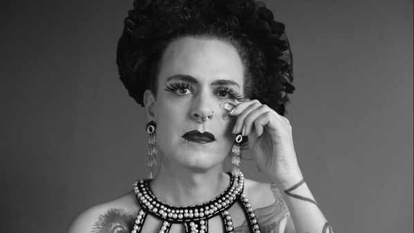 A light skinned non-binary femme person gazes sadly into the camera. They wear extravagant jewellery, heavy make-up, and a headdress but their gaze is solemn and serious. They're applying hormone gel under their left eye.