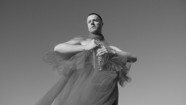 a white man wearing a chiffon fabric dress and holding an over-large glass rosary. Shot from below, he stands out against the clear sky, frowning out of the frame.